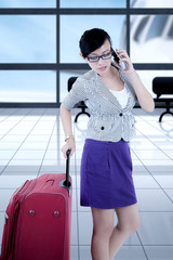 Female entrepreneur using a smartphone in the airport