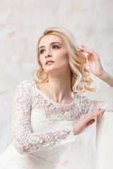 fashionable wedding dress, beautiful blonde model, bride hairstyle and makeup concept - young woman in white gown sitting indoors on light background, luxury female posing in the studio