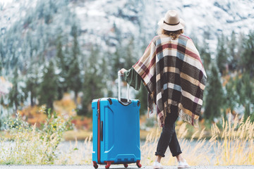 Traveling woman wearing poncho and hat with bright blue suitcase looking at stunning mountain wilderness. Wanderlust and boho style
