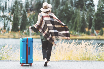 Woman tourist standing in the wind, wearing poncho and hat with bright blue suitcase looking at stunning mountain wilderness. Wanderlust and boho style
