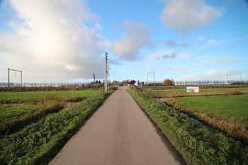 Road in the middle of the Zuidplaspolder at Moordrecht, Netherlands. On horizon there is a railroad crossing and blue sky with white clouds