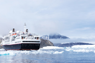 luxury passenger ship sails on icy sea in antarctic in clouds ky