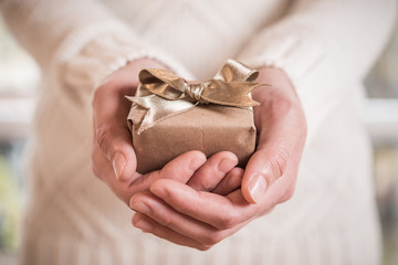Hands holding little gift with golden bow. Close up.