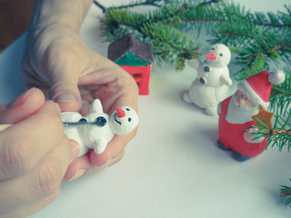 Handmade manufacture of a small toy snowman. Preparations for the celebration of Christmas.