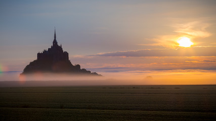 Panoramic view of famous Le Mont Saint-Michel tidal island in beautiful sunrise foggy light, Normandy, northern France