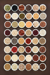 High fibre health food sampler with cereals, nuts, seeds, grain, fruit, herbs and legumes with foods high in omega 3 fatty acid, antioxidants and vitamins, top view. With titles.