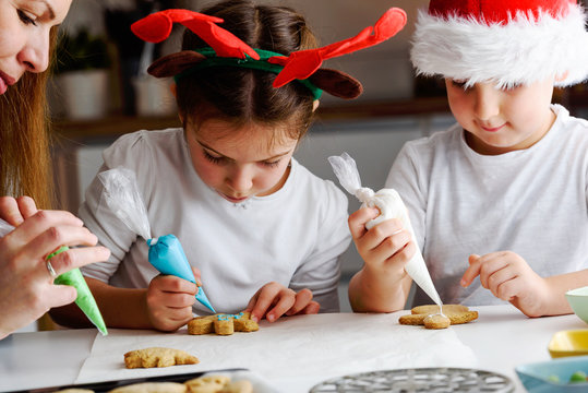 Mother with children baking cookies for Christmass