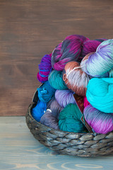 Colourful Yarn balls in the basket on the wooden background