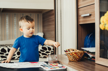 the baby in the nursery, with enthusiasm draws paints