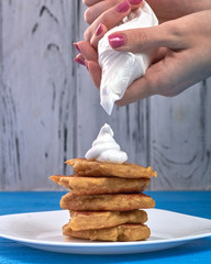 Woman chef squeezes white protein cream on a stack of delicious pancakes. Corn tortillas with whipped cream. Use of a confectionery bag in the kitchen. The process of creating a dessert.
