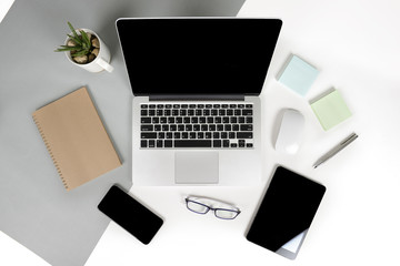 Flat lay photo of Office table with laptop computer, notebook, digital tablet, mobile phone, Pencil, eyeglasses  on modern two tone (white and grey) background. Desktop office mockup concept.