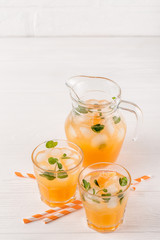 Mandarin cocktail with ice and mint in beautiful glasses and jug, fresh ripe citrus on white wooden background. Sweet orange juice. Close up photography. Selective focus