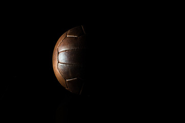 Old football leather ball on a black background