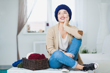 Beautiful woman in big blue knitted hat indoors sit on chest with basket yarn