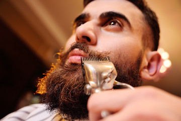 Barber makes a styling beard to the client - a young handsome man with a mustache. Shaving your beard in barbershop