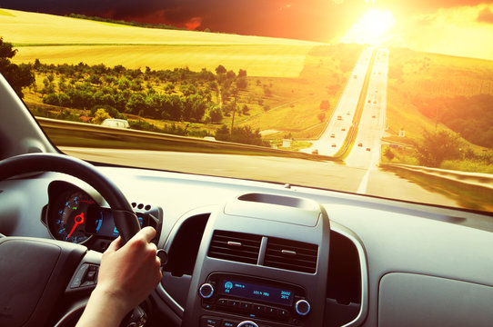 Car dashboard with driver's hand on the steering wheel against road and night sky with sunset