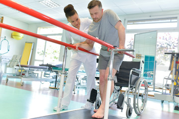 physiotherapist helping patient to walk