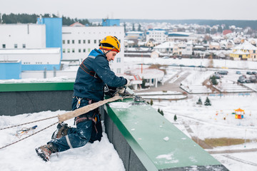 Professional industrial climber in helmet and uniform works at height. Risky extreme job.