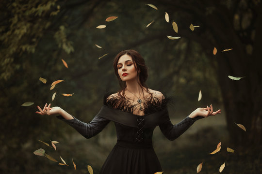 Incredible, amazing, seductive girl, in a black dress , magic rotates the leaves. The background is fantastic autumn. Artistic photography.