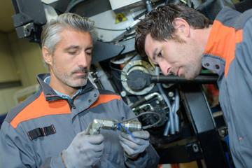 two mechanics working at workshop