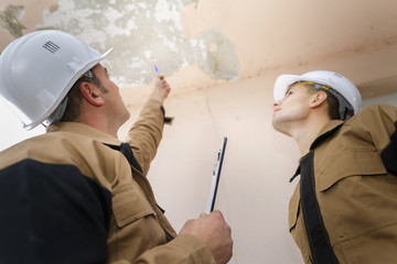 two workers inspecting building ceiling