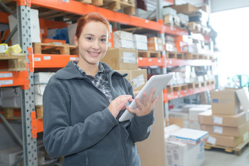 Young warehouse worker holding tablet