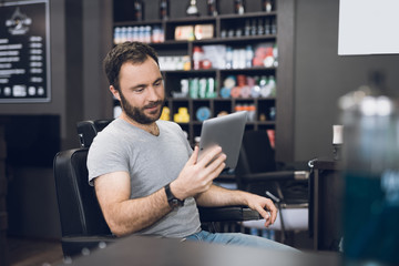 A man looks at the tablet in the barber's chair in a man's barbershop.