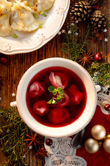 Christmas beetroot soup, borsch with small dumplings with mushroom stuffing in a ceramic bowl, top view.  Traditional Christmas eve dish in Poland.