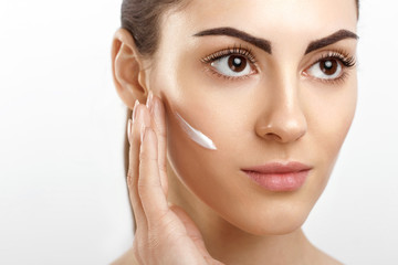 Beautiful Young Woman with Clean Fresh Skin applying cream and touch own face. Facial treatment. Cosmetology. beauty and spa.