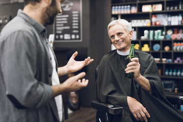 The old man drinks alcohol in the barber's chair in barbershop.