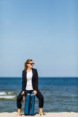 Woman sitting on suitcase on beach