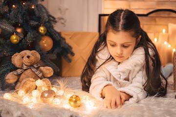 Sad little girl near Christmas tree