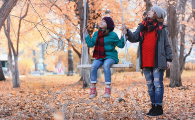 Girl in autumn city park in leaf fall. Young beautiful mother wi