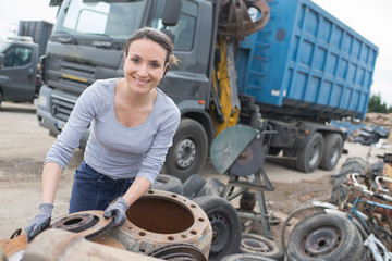 female working at an scrap yard with pile cars