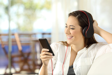 Happy girl listening to music in a beach apartment