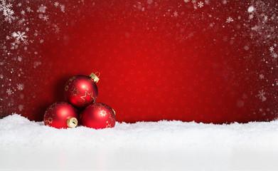 Weihnachtskugeln im Schnee vor rotem Hintergrund