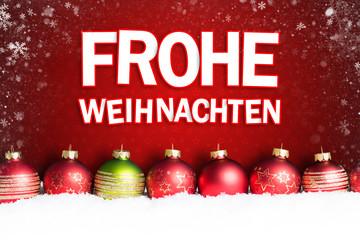 """Weihnachtskugeln im Schnee vor rotem Hintergrund mit """"Frohe Weihnachten"""" Gruß"""