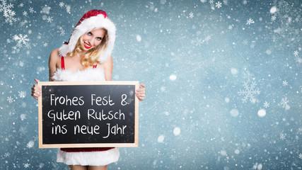 Weihnachtsfrau mit Kreidetafel und Weihnachtsbotschaft vor Winterlandschaft