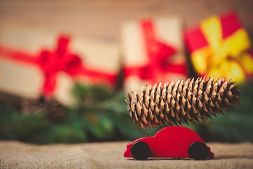 Red toy car with pine cone