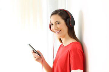 Happy girl listening to music looking at you