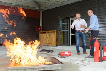 2 workers training in case of fire emergency