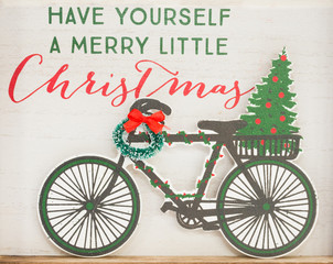 "Close Up of Christmas decoration with a vintage feel showing a bicycle, wreath and the saying ""Have Yourself a Merry Little Christmas""."