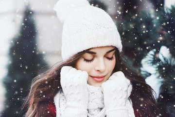 Outdoor close up portrait of young beautiful happy smiling girl wearing white knitted beanie hat, scarf and gloves. Model posing in street. Winter holidays concept. Toned