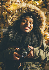 African girl takes photo with vintage camera.