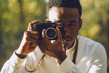 African boy takes photo with vintage camera.