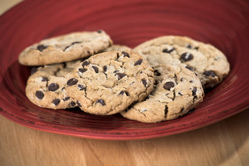 close up of fresh baked chocolate chip cookies on red plate