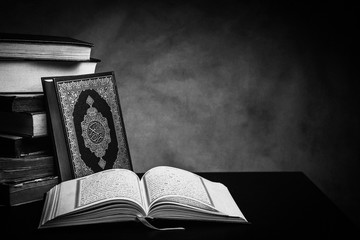 Koran - holy book of Muslims ( public item of all muslims ) on the table , still life Monochrome or black and white