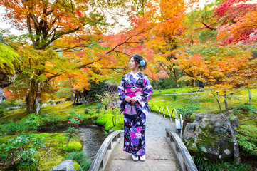 Fototapete - Asian woman wearing japanese traditional kimono in autumn park.