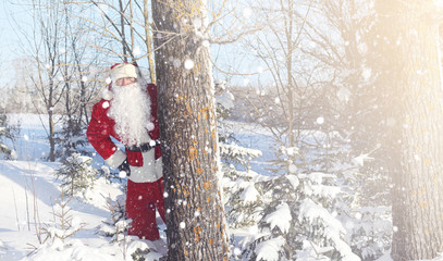 Santa Claus comes with gifts from the outdoor. Santa in a red su