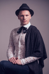 one young Caucasian man, gay gentelman, wearing lace shirt, hat, studio portrait